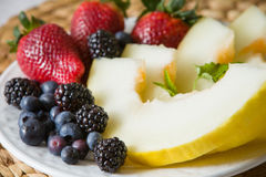 A white plate with fresh organic fruit. Stock Photos