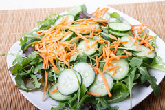 White Plate of Fresh Salad on Bamboo Mat Royalty Free Stock Images