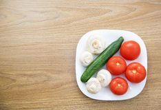 White plate with fresh tomatoes, mushrooms and cucumbers on a wooden table. Top view Stock Photos
