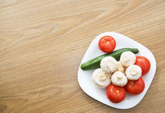 White plate with fresh tomatoes, mushrooms and cucumbers on a wooden table. Top view Royalty Free Stock Photos