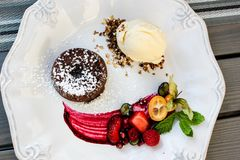 Delicious chocolate cake with ice cream and berries in spring 2019. White plate with freshly made chocolate cake with vanilla ice cream scone with berries and royalty free stock image