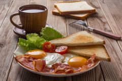 White plate of fried eggs with bacon, toasts and vegetables on wooden table. Wooden cup of tea. Close up. Soft focus royalty free stock images