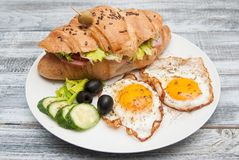 White Plate with Fried Eggs and Croissant Sandwich with Cucumber, Tomatoe and Olives. Breakfast. Gray Wooden Background. Rustic St Royalty Free Stock Photos