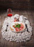 A white plate full of prosciutto, cheese, nuts and a wineglass on white stones and on a wooden background. Expensive Royalty Free Stock Photography