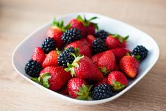White plate full of strawberries and blackberries Stock Photos