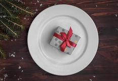 White plate with a gift wrapped, top view Royalty Free Stock Photography