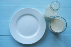 White plate, glass and bottle with milk Royalty Free Stock Image