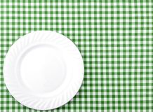 White Plate on Green and White checkered Fabric Tablecloth Backg. Round Stock Images