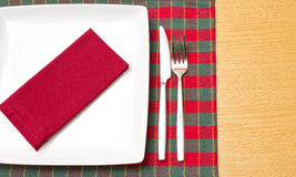 White plate on green and red tablecloth Stock Photography