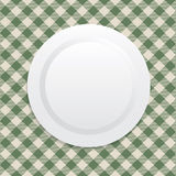 White plate on green tablecloth Stock Photo