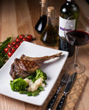 White plate with grilled steak on a bone. On a wooden table, surrounded by decor stock photos