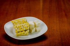 White plate with half of cooked corn cob lying on Royalty Free Stock Photo