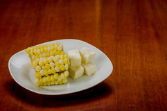 White plate with half of cooked corn cob lying on Royalty Free Stock Image