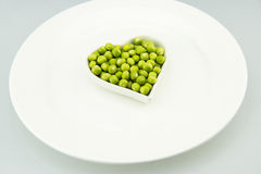 The white plate, a heart-shaped small, fresh peas  Royalty Free Stock Images