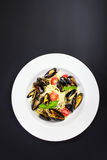 White plate of italian pasta with mussels, cherry tomato  and he Royalty Free Stock Photos