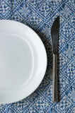 White plate and knife. A white plate and silver knife on blue texture Stock Images