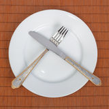 White plate, knife and fork Royalty Free Stock Photos