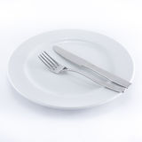 White plate, knife and fork Royalty Free Stock Images