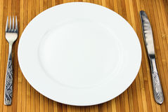 White plate, knife and fork at bamboo napkin Stock Images