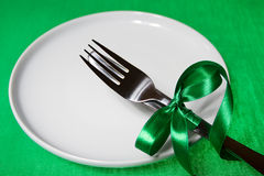 White plate knife and fork with gibbon over green. White plate with knife and fork with green gibbon over green background Stock Images
