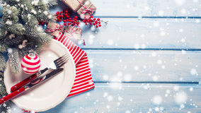 White plate, knife and fork, napkin and christmas decorations in Royalty Free Stock Image