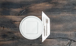 White plate, knife, fork, napkin. Empty dishes wooden background Royalty Free Stock Photography