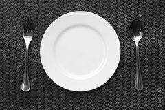 White plate, knife and fork at napkin on wooden Royalty Free Stock Photos