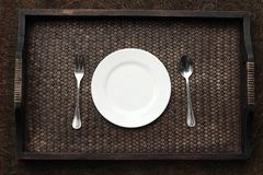 White plate, knife and fork at napkin on wooden Royalty Free Stock Photography