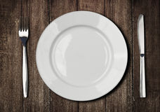 White plate, knife and fork on old wooden table royalty free stock photos