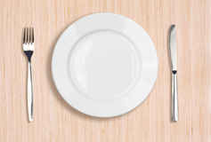 White plate, knife and fork top view on table Royalty Free Stock Photo