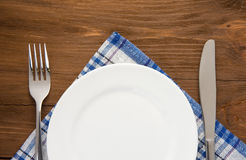 White plate, knife and fork on wood Royalty Free Stock Image