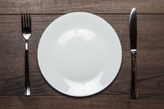 White plate with knife and fork on wooden table Royalty Free Stock Photo