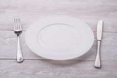 White plate, knife and fork Stock Photos