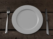 White plate, knife and fork on wooden table Royalty Free Stock Images