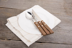 White plate, knife, spoon and fork at napkin on wooden backgroun Royalty Free Stock Image