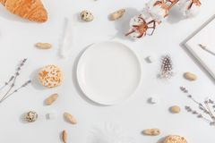 White plate on a light background. Composition with lavender, cotton and nuts stock images