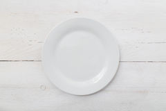 White plate on light wood Royalty Free Stock Image