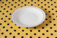 White plate on light yellow polka dot background Stock Images