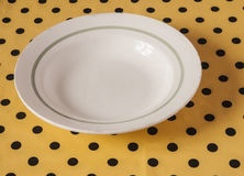 White plate on light yellow polka dot background Stock Photography