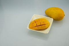 The white plate and mango. A square plate square white, has dialed the skin of mango, there is no dial skin plate of mango stock photo