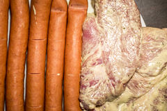 White plate with meat for grilling bbq Sausages, steak close up raw ready for fire Stock Photo