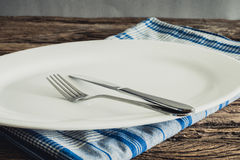 White Plate on a napkin and silver  fork , knife. on wooden tabl Stock Images