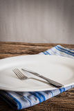 White Plate on a napkin and silver  fork , knife. on wooden tabl Stock Photos