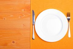 White plate next to fork knife on a napkin on a wooden board top Royalty Free Stock Photos