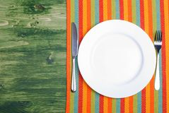 White plate next to fork knife on a napkin on a wooden board top Stock Photos