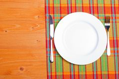 White plate next to fork knife on a napkin on a wooden board top Stock Images