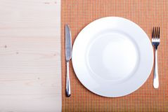 White plate next to fork knife on a napkin on a wooden board top Stock Photography