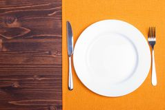 White plate next to fork knife on a napkin on a wooden board top Royalty Free Stock Photo