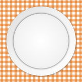 White plate on orange tablecloth Royalty Free Stock Image