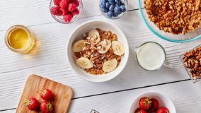 A glass of milk, juicy different berries, honey and a plate with granola and banana slices on a white wooden table Royalty Free Stock Photos